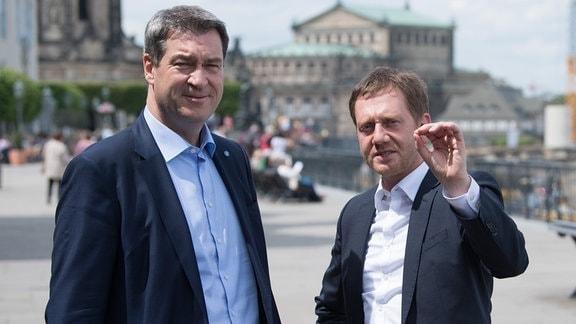 Markus Söder (li.) und Michael Kretschmer stehen auf der Elbpromenade in Dresden.