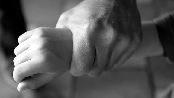 Eine Männerhand hält eine Kinderhand fest