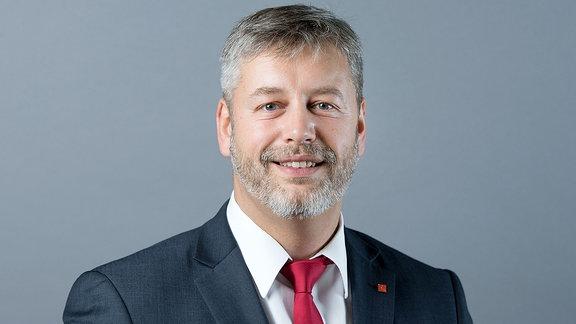 Albrecht Pallas SPD steht vor einer Fotowand.
