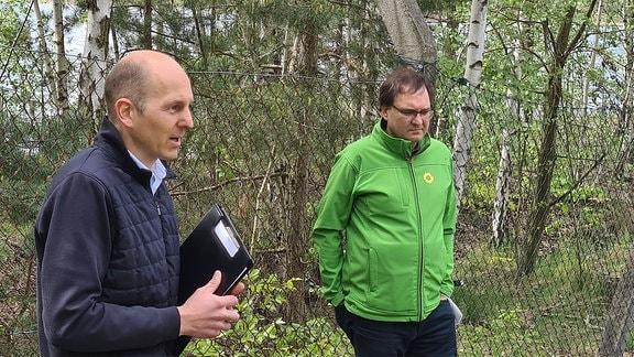 Anwohner und Bündnisgrüner Jens Bitzka vor Maschendrahtzaun.
