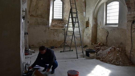 Restaurator in der Vorkirche während der Sanierung