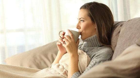 Frau auf Sofa Tee trinken