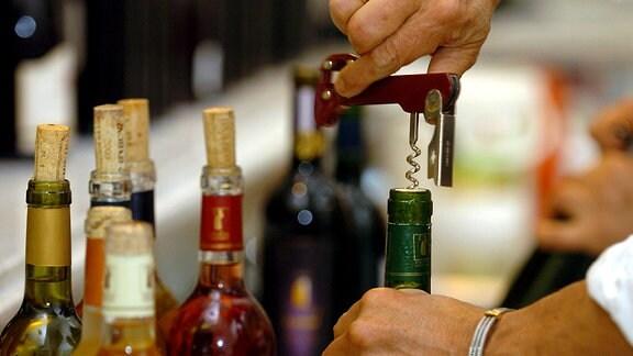 Ein Mann öffnet eine Flasche Wein