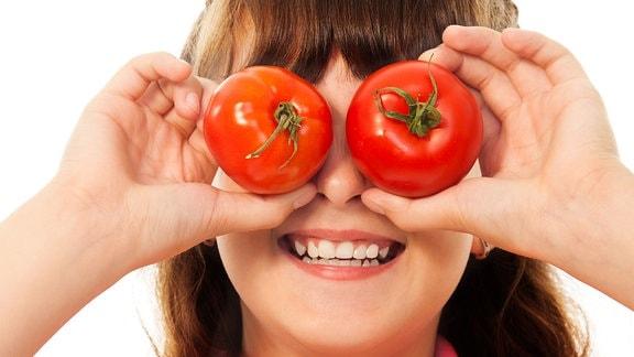 Lachendes Kind hält sich 2 Tomaten vor die Augen.