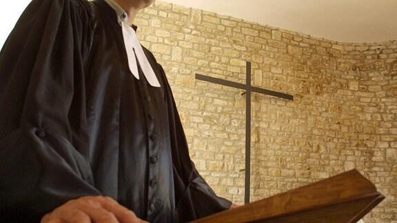 ein Pfarrer steht in der Kirche