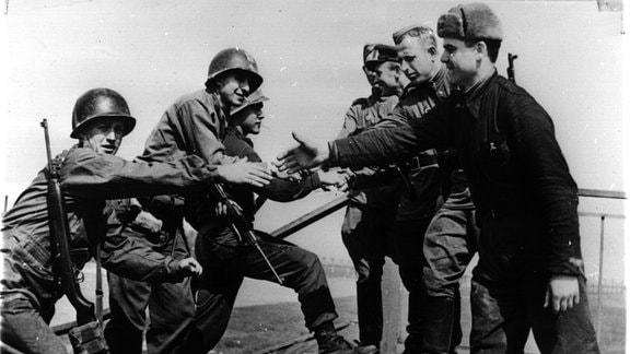 Händedruck zwischen Rotarmisten und US-Soldaten auf der zerstörten Brücke über die Elbe bei Torgau.