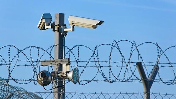 Überwachungskameras hinter einem Drahtzaun mit Stacheldraht