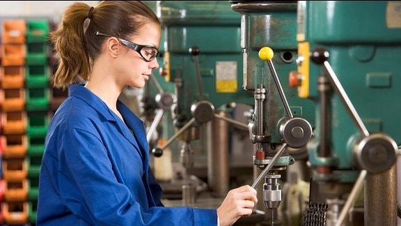 Ein junge Frau arbeitet an einer Bohrmaschine.