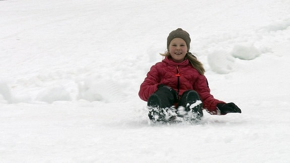 Mädchen beim Rodeln im Schnee