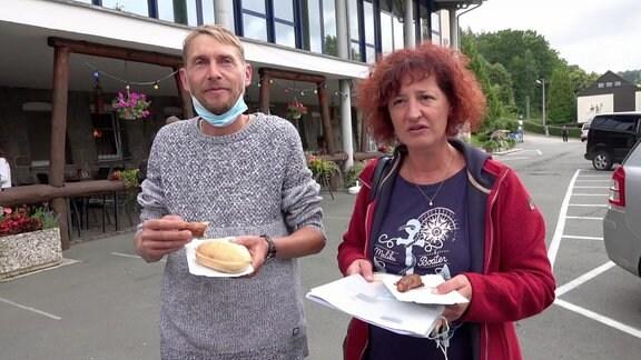 Ein Mann mit dunkelblondem Haar und grauem Pullower isst eine Bratwurst. Dabeben steht seine Frau mit rötlichem Haar sowie roter Strickjacke und dunkelblauem T-Shirt.