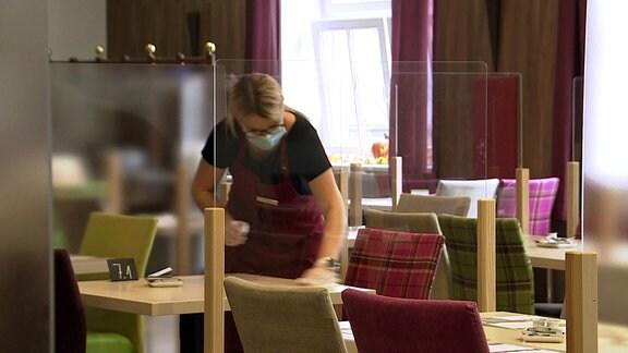 Eine Hotelangestellte putzt mit Mundschutz Tische, auf denen Plexiglaswände stehen.