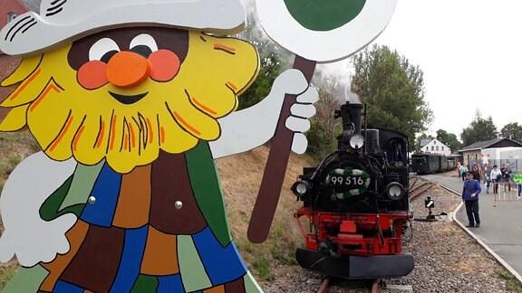 Das Maskottchen Wurzelrudi vor der Museumsbahn.