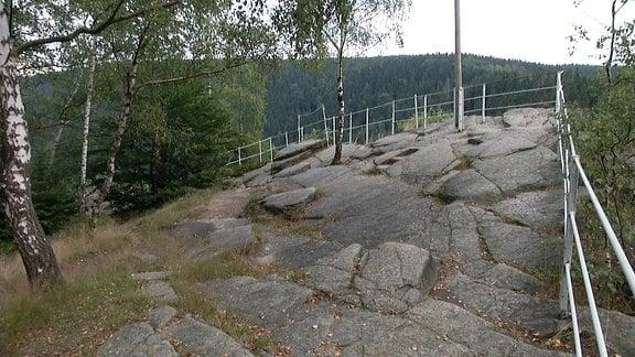 Man sieht eine steinerne Aussichtsplattform auf einem Felsen. Dahinter liegt ein bewaldetes Tal