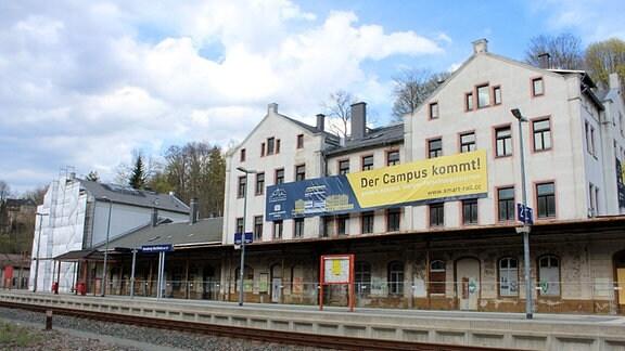 """An einem teilweise eingerüsteten Bahnhof hängt ein Plakat; """"Der Campus kommt!"""""""