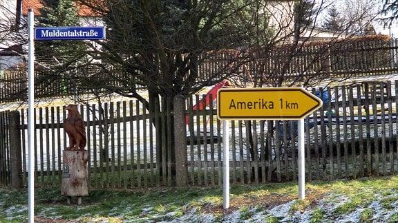 n einer Straße steht ein pfeilförmiger Wegweiser, auf dem das Wort Amerika zu lesen ist