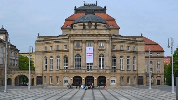 Auf dem Theaterplatz vor der Oper Chemnitz haben sich mehrere Menschen zu einer Pressekonferenz versammelt.