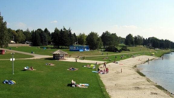 Totale auf die Wiesenliegeflächen am Stausee Rabenstein. Es sind schätzungsweise 50 Gäste zu sehen
