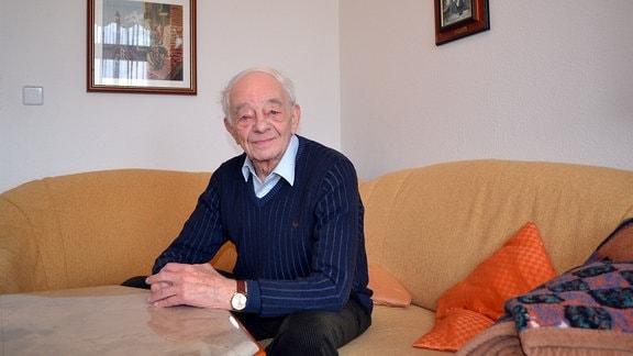 Ein älterer Herr sitzt auf einer Wohnzimmercouch und blickt in die Kamera