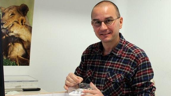 Biologe Sven Erlacher vom Naturkundemuseum Chemnitz sitzt an einem Schreibtisch vor einem Glaskasten mit Schmetterlingspräparaten