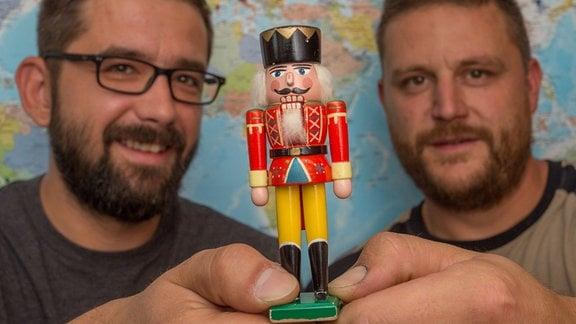 Zwei Männer halten einen Nussknacker in den Händen.