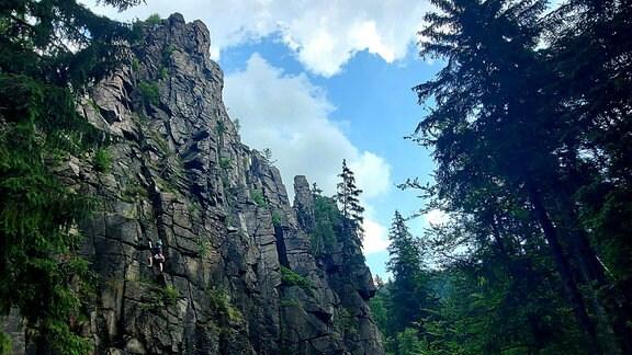 Eine Felswand ragt steil aus einem Tal empor. Sie trägt den Namen Nonnenfelsen und ist im Schwarzwassertal im Erzgebirge zu finden.