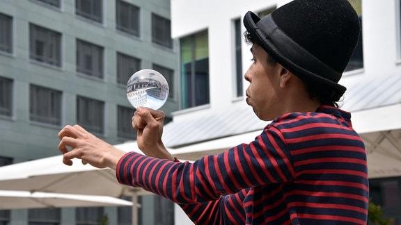 ein Künstler mit einer Glaskugel auf der Hand bei Hutfestival Chemnitz