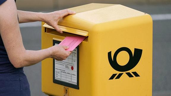 Eine Hand wirft einen Brief zur Briefwahl in einen Briefkasten.