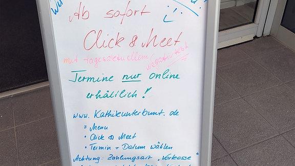 Hinweistafel mit Anleitung zum Ablauf Click & Meet steht vor einem Geschäft.