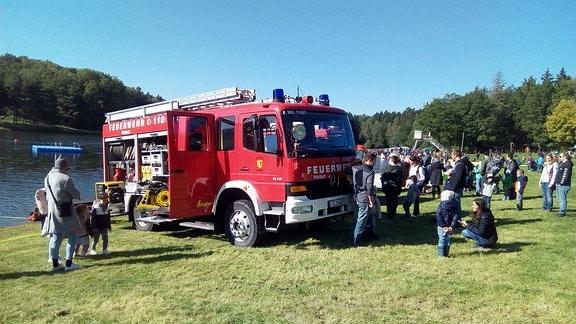 Ein Löschfahrzeug der Feuerwehr steht auf einer Wiese am Ufer eines Sees, daneben sind Kinder.