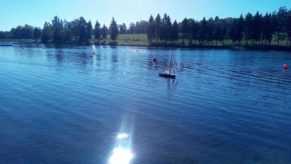 Ein Modellsegelboot im Gegenlichtfährt auf einem kleinen See.