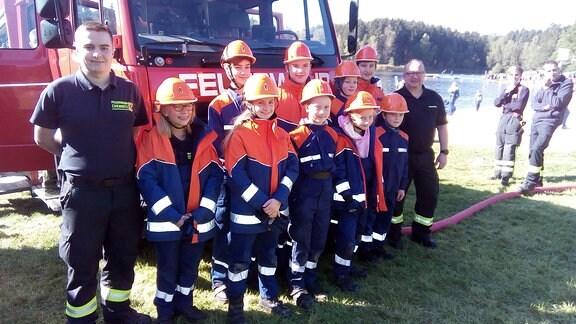 Eine Gruppe Kinder in Feuerwehruniform steht vor einem Feuerwehrfahrzeug.