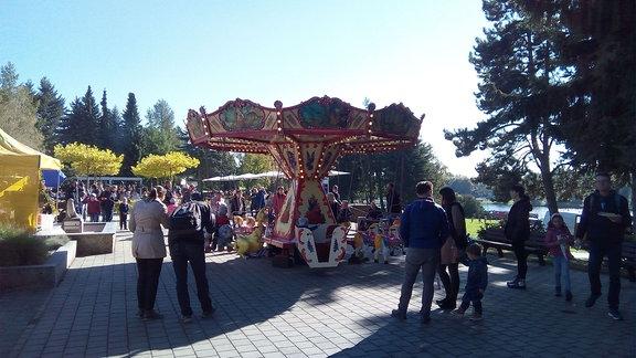 Eltern mit ihren Kindern stehen um ein Kinderkarussel, einige Kinder fahren mit.