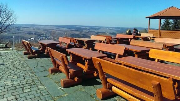 Auf einem Berplateau stehen viele unbesetzte Bänke und Tische eines Ausflugslokals