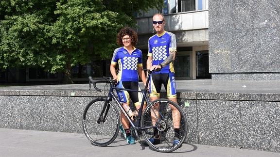 Eine Frau und ein Mann in Radfahrerkleidung stehen lachend mit einem Rennrad vor einem Steinsockel.