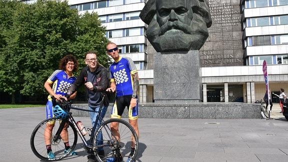 Vor dem Karl-Marx-Monument in Chemnitz stehen ein Mann und eine Frau in Radfahrerkleidung und ein weiterer Mann hinter einem Rennrad.