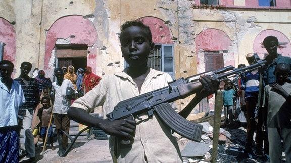 Ein Kind posiert mit einer AK-47 vor einem zerschossenen Haus in Mogadishu
