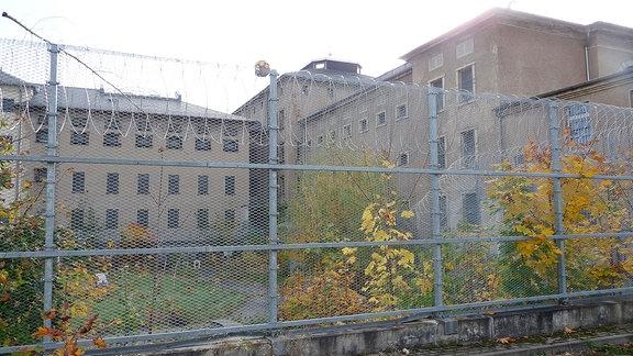 Hinter einem Stacheldrahtzaun sind Gebäude des Chemnitzer Kaßberg-Gefängnisses sichtbar.