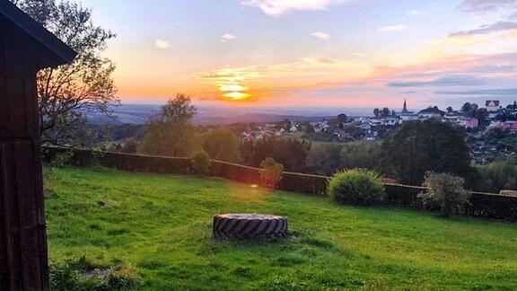 Von einer Wiese aus blickt man in ein Tal und sieht in der Ferne eine Kleinstadt im Erzgebirge. Am Himmel geht die Sonne unter und färbt alles orange-rot ein.