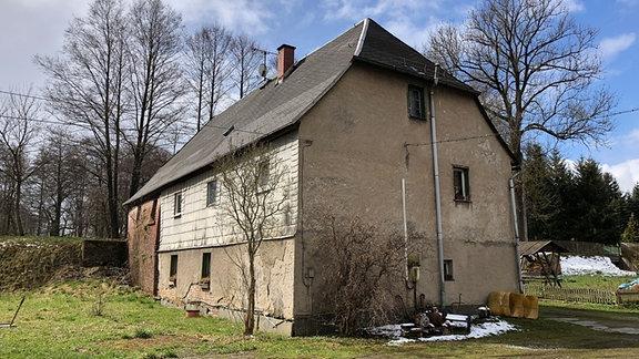 Von einem alten Gebäude mit Walmdach blättert der Putz, eine Wand wölbt sich nach außen.