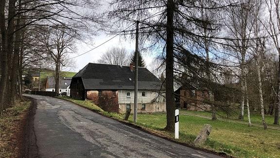 Eine Straße führt unmittelbar am Giebel eines tiefergelegenen alten Hauses vorbei.