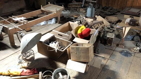Auf einem Dachboden liegen alte, eingestaubte Alltagsgegenstände in Kartons.