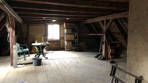Auf einem alten Dachboden mit Gerümpel tragen dicke Balken eine alte Holzdecke.