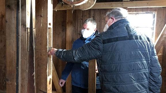 Zwei Männer betrachten historische Mühlentechnik in einem alten Gemäuer.
