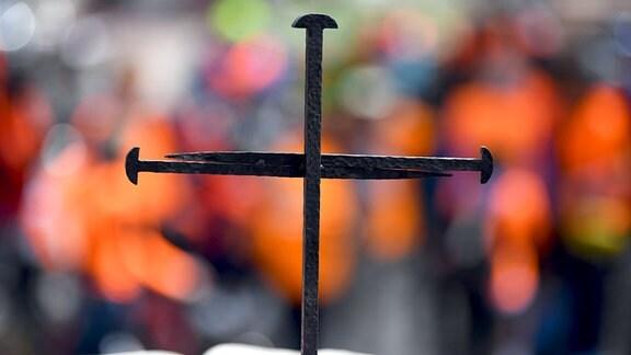 Ein Nagelkreuz steht am 24.05.2017 in Berlin vor einer Bibel auf einer Bühne vor der Gedächtniskirche.