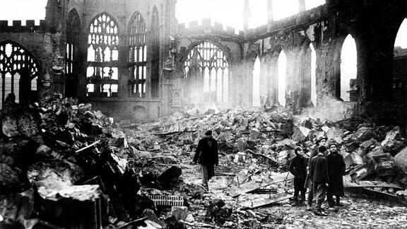 Menschen stehen 1940, nach einem Bombenangriff, in den Ruinen der zerstörten Kathedrale in Coventry.
