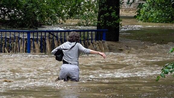Eine Frau watet durch das Wasser, das ihr bis an die Oberschenkel reicht.