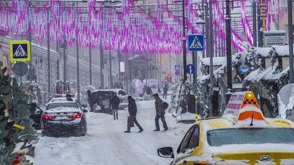 Menschen auf einer zugeschneiten Straße