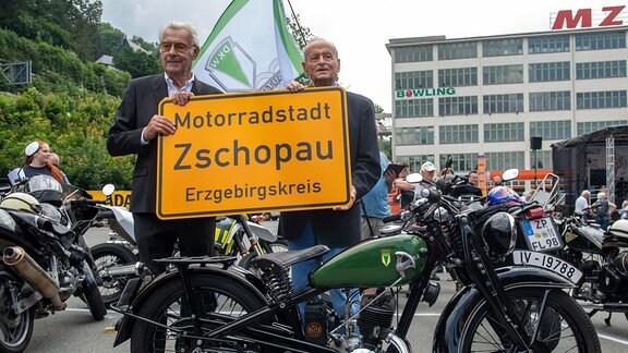Jörgen S. Rasmussen und Carl Hahn stehen an einer DKW SB 200 von 1936 vor dem einstigen Motorradwerk von DKW und MZ in Zschopau mit dem neuen Ortseingangsschild der Motorradstadt.