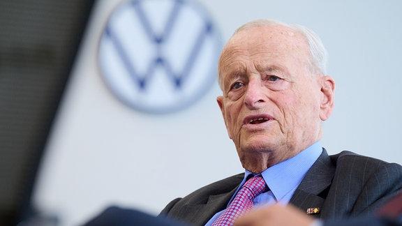 Portrait von Professor Dr. Carl H. Hahn, einem älteren Herrn mit Krawatte und Anzug, vor einem VW-Logo.