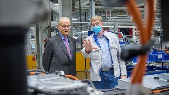 Professor Hahn steht mit Holger Hollmann in einer hellen Montagehalle